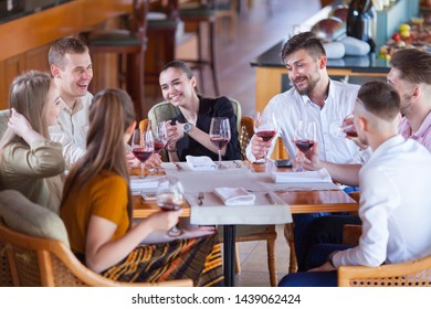 company of friends celebrates meeting in a restaurant