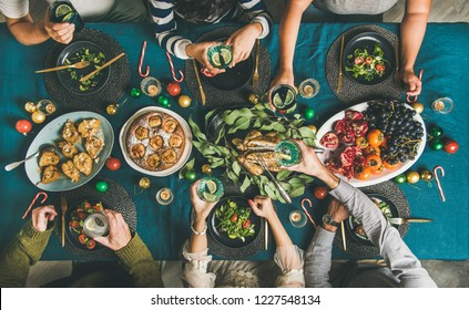Company of friends of different ages gathering for Christmas or New Year party dinner at festive table. Flat-lay of human hands holding glasses with drinks, feasting and celebrating holiday, top view