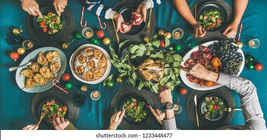 Company of friends of different ages gathering for Christmas or New Year party dinner at festive table. Flat-lay of human hands eating meals and celebrating holiday, top view