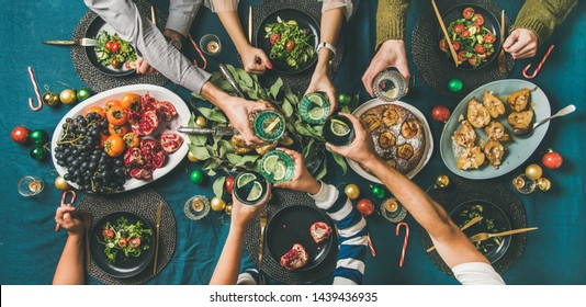 Company of friends of different ages gathering for Christmas or New Year party dinner at festive table. Flat-lay of hands holding glasses with drinks, feasting and celebrating holiday, top view