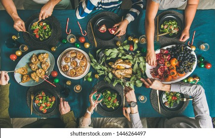 Company of friends of different ages gathering for Christmas or New Year party dinner at festive table. Flat-lay of human hands holding glasses with drinks, eating and celebrating holiday, top view