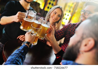 A company of friends drink beer and clink glasses at a pub