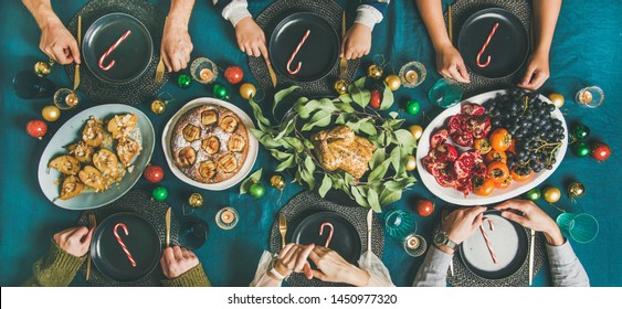 Company of friends gathering for Christmas or New Year party dinner at festive table. Flat-lay of people sitting with plates and ready to start celebrating holiday together, top view, wide composition