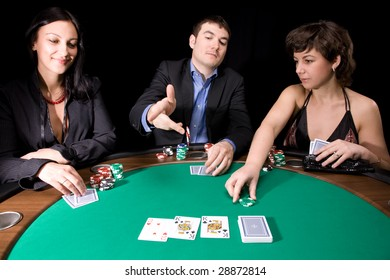 Company of friends having fun with the casino poker table
