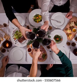 Company of friends having fun at dinner in a restaurant. On the table a variety of dishes from the chef. They clicked their glasses of wine. Conceptual photographyView from above
