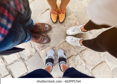 company of friends wearing different shoes, view from above, sneakers, boots, autumn fashion trend, close up legs, details, men and women standing together