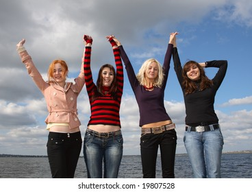 Company of girls having fun on green grass