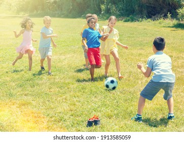 Company of glad children playing football on the playground in park