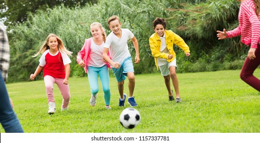 Company of glad kids playing football on the playground in park