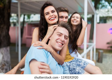 A company of good-looking friends is laughing and sitting on the railing in the nice summer cafe. Entertainment, having good time. Friendship.