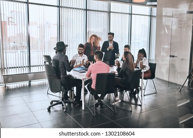 company is greeting foreign partner. happy diverse people are sitting at the table and clapping hands in the room with panorama window