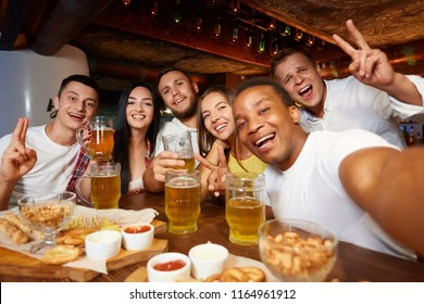 Company of happy friends wearing in casual clothes, taking self portrait with peace sign gesture and drinking beer, eating snacks at bar. Four boys and two girls smiling and enjoying time together.