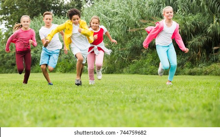 Company of happy kids are jogning together in the park.