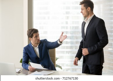 Company leader dissatisfied with work results pointing on door to perplexed employee. Boss informing about demotion, reducing wages, making verbal warning for poor performance, firing office worker