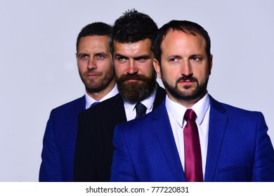 Company leaders stand for their businesses. Board of executives present strength. Business, confidence and teamwork concept. Businessmen with strict faces in formal wear on grey background