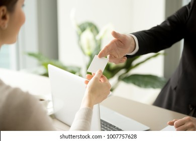 Company male manager giving blank business card over work desk with laptop to female client or business partner. Business leaders exchanging their contacts on meeting in office. Back view. Close up