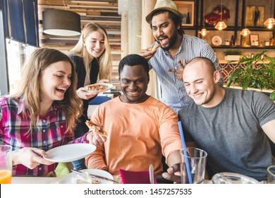 A company of multicultural young people in a cafe eating pizza, drinking cocktails, having fun