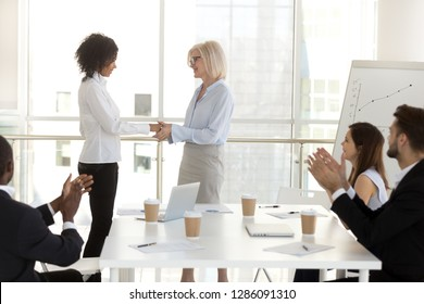 Company owner aged boss female handshaking with young biracial woman congratulating successful worker with promotion. Diverse business people colleagues applauding greeting supporting intern newcomer