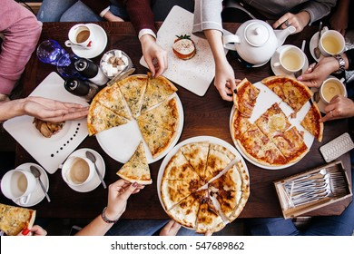 company of people eating pizza. top view