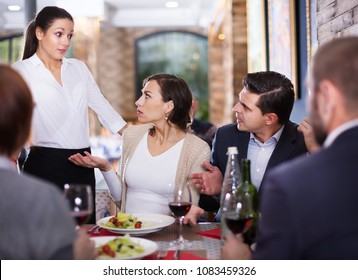 Company of people expressing dissatisfaction with a waitress about food