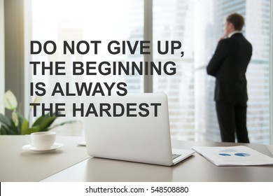 """Company president in formal suit standing, looking through window at cityscape, dreaming. Photo with motivational text """"Do not give up, the beginning is always the hardest"""". Business success concept"""