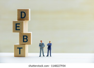 Company secured and unsecured debt, financial distress concept : Miniature figurine 2 bussinessmen CEO, CFO talk together on high interest rate debt and method to handle and avoid becoming bogged down