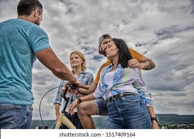 Company stylish young people spend leisure outdoors sky background. Couple meet cheerful friends with bicycle during walk. Cycling modernity and national culture. Group friends hang out with bicycle.