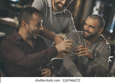 Company of three friends clinking crystal glasses, laughing and looking at each other. Men spending time together in bar, communicating and talking. Friends drinking delicious alcohol.