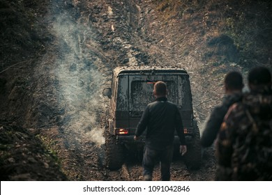 Company of three men looks at suv drives with clouds of smoke. Car covered with mud on path with deep rut. Offroad car with dirt on background. Extreme entertainment concept.