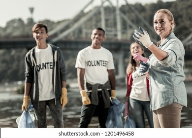 Company of volunteers. Company of mature blonde-haired team leader and three young volunteers cleaning up the beach