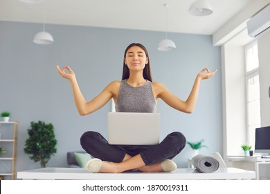 Company worker with positive mindset sitting on office desk with laptop in easy yoga pose during break, meditating and relaxing. Woman practicing mindfulness, reducing stress, reaching peace of mind