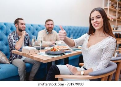 The company of young guys and girls in a cafe, the girl smiles and shows her thumb up.