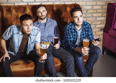 The company of young men drink beer and watch TV.
