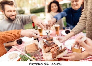 A company of young people came together for a barbecue. Friends have fun, they cook food, drink alcohol. They gathered in nature on a sunny day.