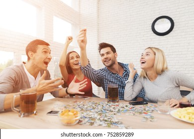The company of young people is folding the image. On the table they have puzzles and stand glasses with alcoholic beverages. They have fun playing a game.