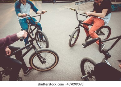 Company of young people on BMX. Beautiful background