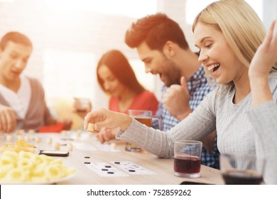 The company of young people is playing in russian lotto. On the table they have glasses with alcoholic drinks. They have fun playing a game.