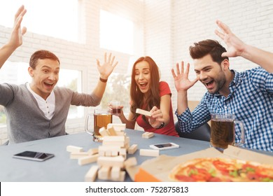 The company of young people plays a table game called jenga. They also eat and drink alcoholic beverages. They are all friends and they are in a good mood.