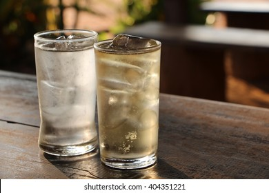 Compare a glass of water and a glass of whiskey and soda on ice.