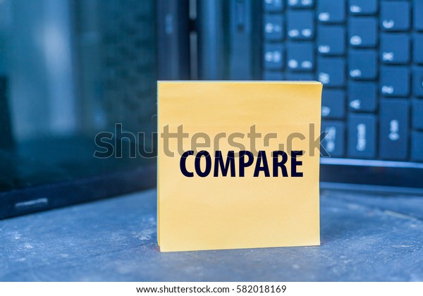 COMPARE word on paper note on wooden table over blurry laptop as a background