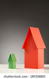 Comparing energy label for homes - small green paper house next to a large red one.