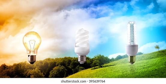 Comparison between various types of light bulb on landscape background. CO2 emissions and environmental conservation. Horizontal composition. Front view