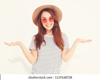 Comparison concept. Young brunette woman in casual hipster clothes and brown hat displaying something on both flat hands for similar choice of product, isolated on white. In sunglasses