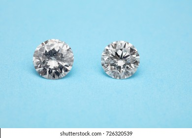 comparison of loose brilliant diamonds, one is flawless, another has many flaws on blue background