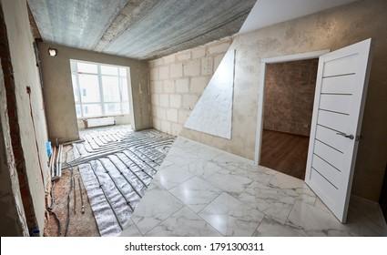 Comparación de la nueva habitación renovada con la puerta abierta y el antiguo lugar con una gran ventana y tubos de calefacción por suelo radiante. Moderno apartamento antes y después de la restauración. Concepto de renovación domiciliaria.
