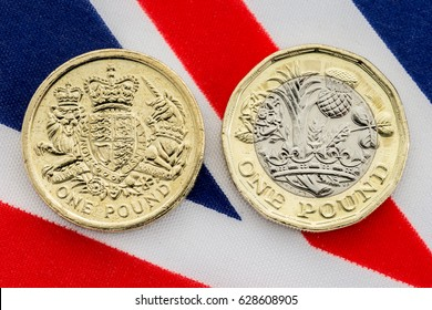Comparison of old and new tails side of British pound coin on a Union Jack flag background. The new coin introduced in March 2017 has many new features to prevent fraud including being bimetallic.