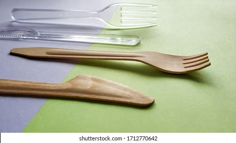 Comparison of plastic and bamboo wooden fork and knife. Eco-friendly disposable cutlery. Caring for the environment