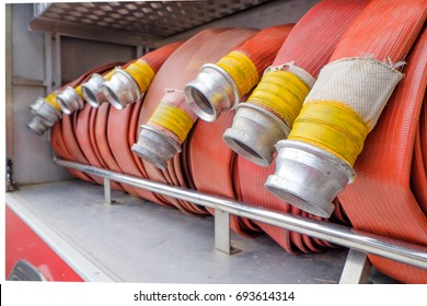 Compartment of rolled up fire hoses on a fire engine. Rescue fire truck equipment.