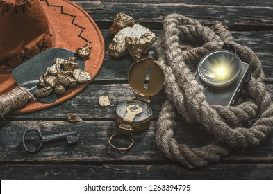 Compas, gold nuggets on the spade, rope and flashlight on the aged wooden table background. Treasure hunter or goldminer concept.