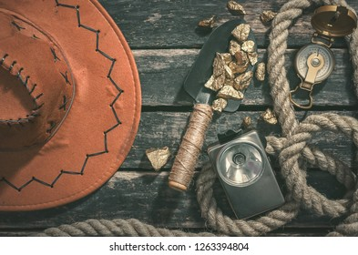 Compas, gold nuggets on the spade, rope and vintage flashlight on the aged wooden table background. Treasure hunter or goldminer concept.